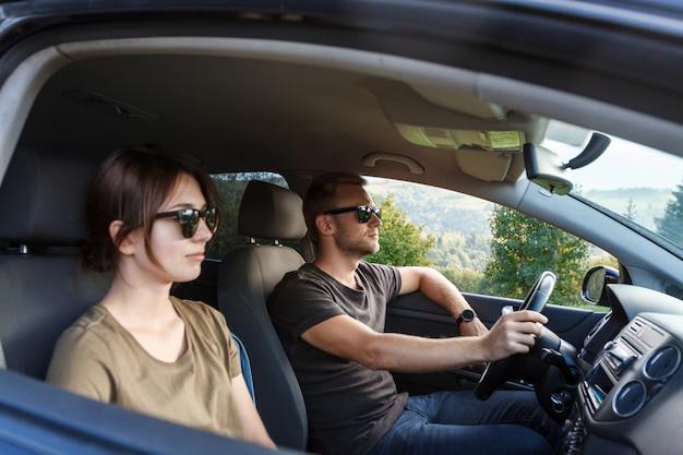 Giovani coppie che sorridono, sedendosi in automobile, godendo del mountain view