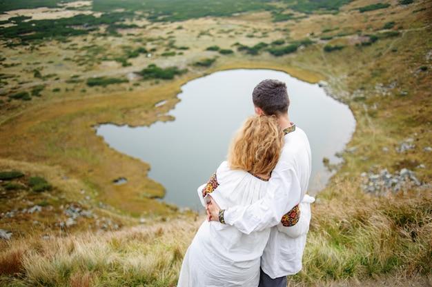 Giovani coppie che stanno abbraccianti sulla collina, godenti della natura