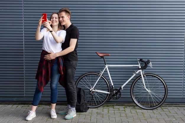 Giovani coppie che stanno con una bicicletta contro lo sfondo del muro