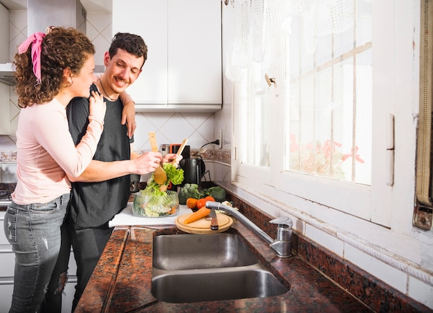 Giovani coppie che stanno vicino al piano di lavoro della cucina che prepara alimento