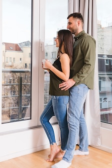 Giovani coppie che stanno vicino alla finestra di vetro