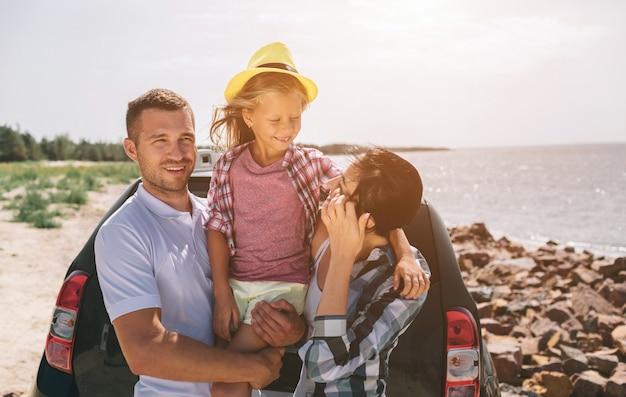 Giovani coppie che stanno vicino allo stivale aperto dell'automobile con le valigie e le borse. papà, mamma e figlia viaggiano in riva al mare o sull'oceano o sul fiume. giro estivo in automobile