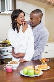 Giovani coppie che stringono a sé nella cucina