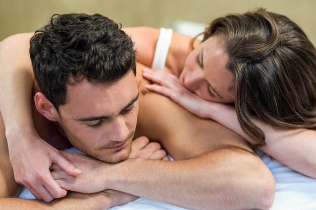 Giovani coppie che stringono a sé sul letto in camera da letto
