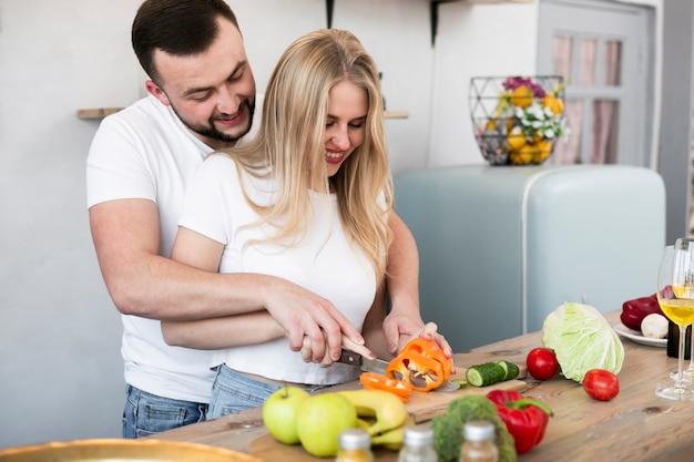 Giovani coppie che tagliano il peperone dolce