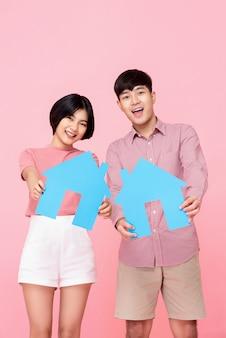 Giovani coppie che tengono i simboli della casa