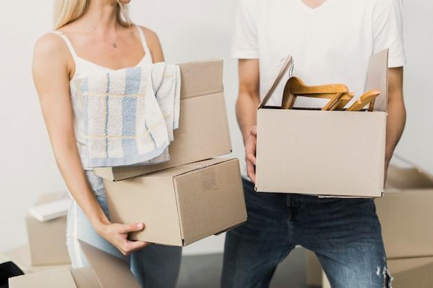 Giovani coppie che tengono insieme le scatole