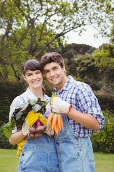 Giovani coppie che tengono le verdure appena raccolte in giardino