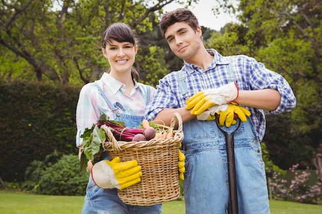 Giovani coppie che tengono un canestro delle verdure appena raccolte in giardino