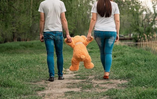 Giovani coppie che tengono un orsacchiotto nel parco
