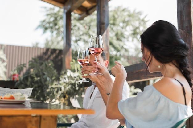 Giovani coppie che tostano i vetri di vino nel giardino