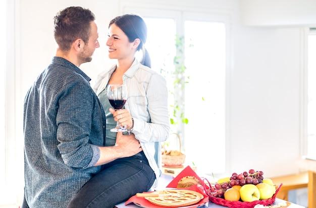 Giovani coppie che tostano vino rosso sulla cucina tenera di momento a casa