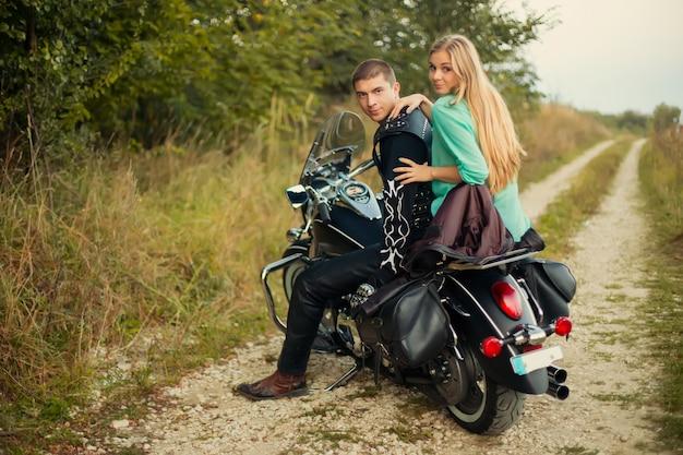 Giovani coppie con bella motocicletta sulla strada.