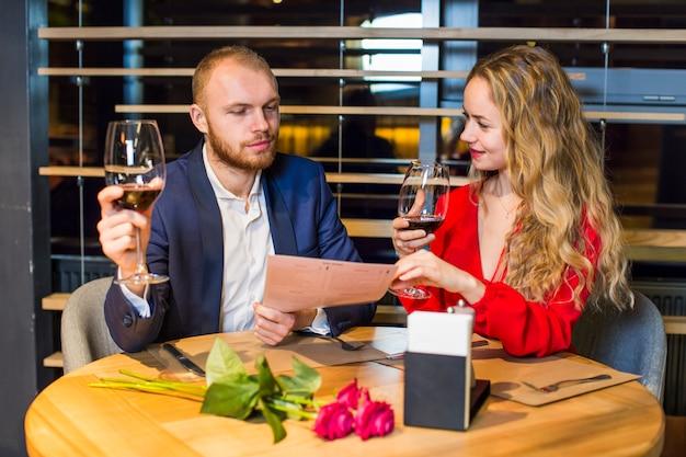 Giovani coppie con i vetri di vino che leggono menu