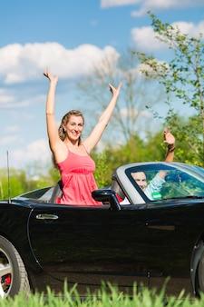 Giovani coppie con il cabriolet di estate sull'escursione di un giorno