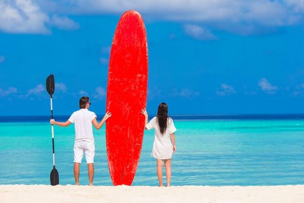 Giovani coppie con il surf rosso durante le vacanze tropicali