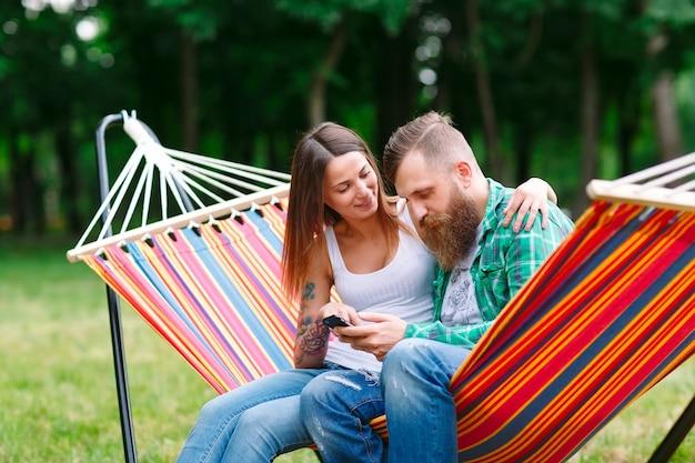 Giovani coppie con il telefono cellulare che si siede sull'amaca