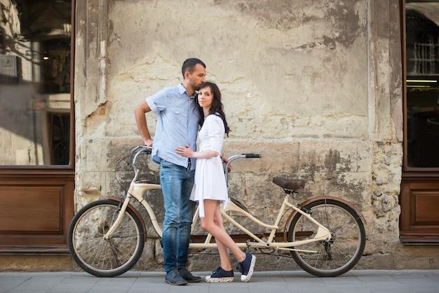 Giovani coppie con la retro bicicletta in tandem alla città della via