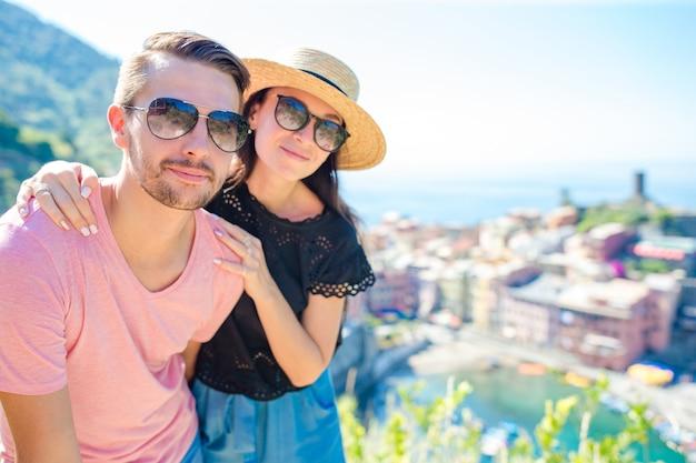 Giovani coppie con la vista di vecchio villaggio costiero nel parco nazionale di cinque terre, liguria, italia, europa