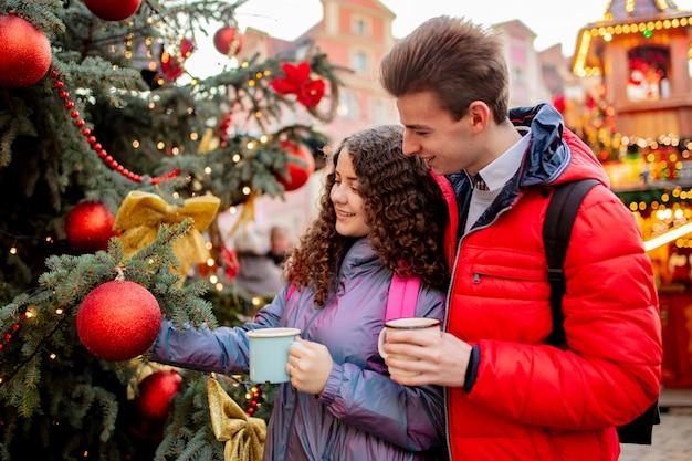 Giovani coppie con le bevande sul mercato di natale a wroclaw, polonia