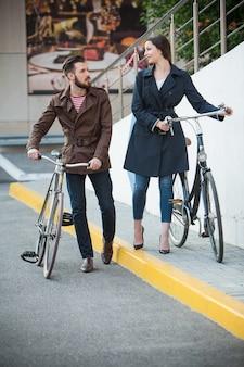 Giovani coppie con una bicicletta di fronte alla città
