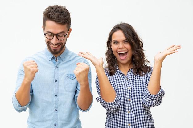 Giovani coppie contente che celebrano successo