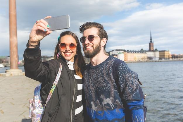 Giovani coppie dei pantaloni a vita bassa che prendono un selfie a stoccolma
