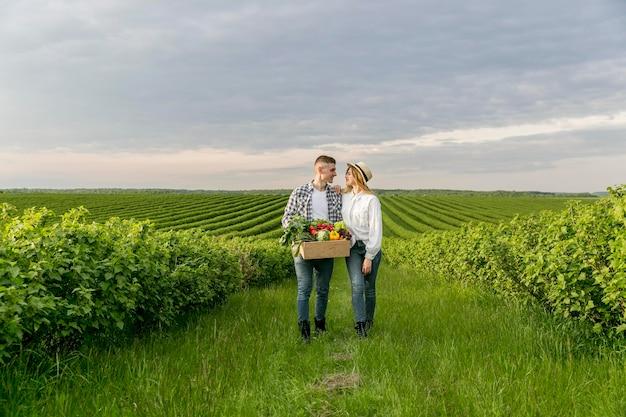 Giovani coppie dell'angolo alto all'azienda agricola