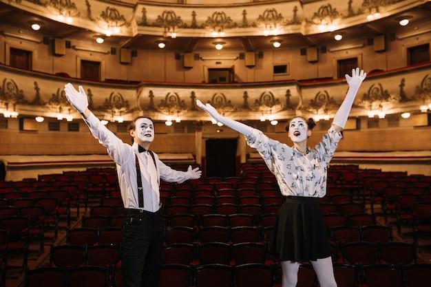 Giovani coppie della mima che stanno nell'auditorium che alza le loro armi