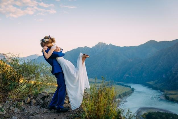 Giovani coppie della persona appena sposata che abbracciano sulla vista perfetta delle montagne e del cielo blu