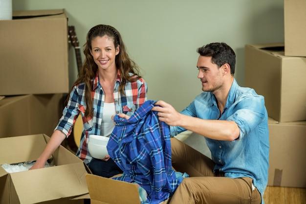 Giovani coppie disimballaggio scatole di cartone nella loro nuova casa