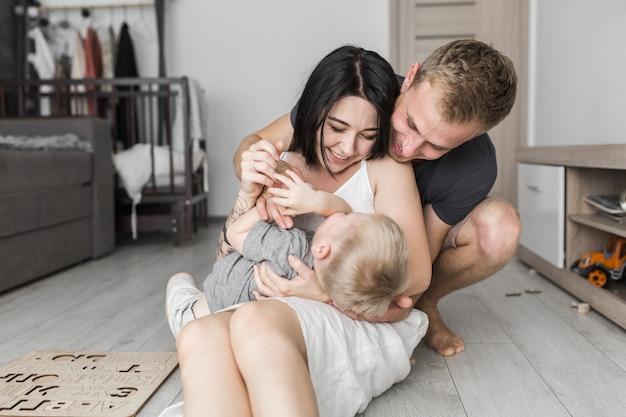 Giovani coppie divertendosi con il loro piccolo figlio a casa