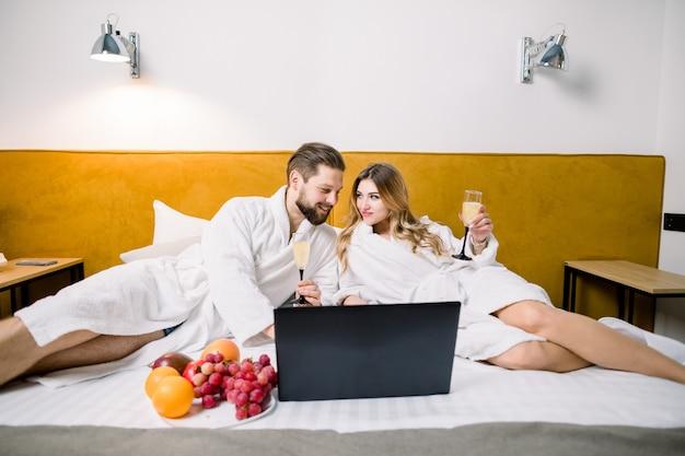 Giovani coppie divertendosi seduta insieme al computer portatile sul letto nella camera d'albergo, mangiare frutta e bere alcolici