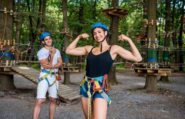 Giovani coppie divertendosi tempo nel parco della corda di avventura.