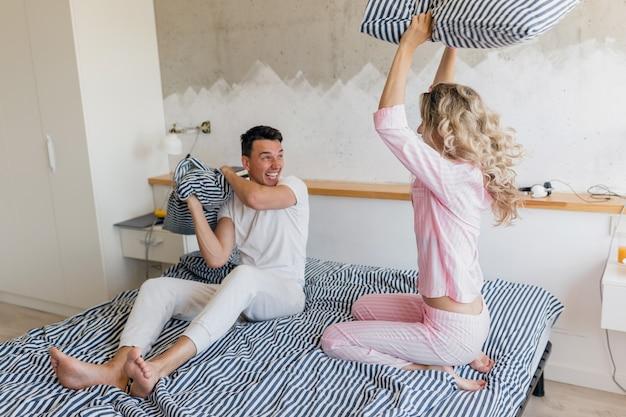 Giovani coppie divertenti divertendosi sul letto la mattina, combattendo con i cuscini, giocando, sorridendo felice