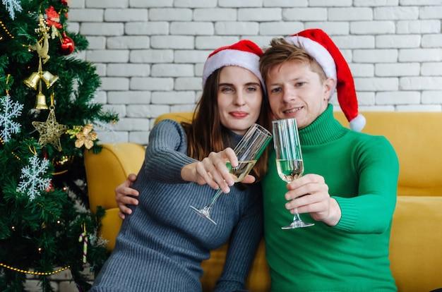 Giovani coppie dolci con il cappello rosso di santa che beve champagne, abbracciando la sua ragazza con l'albero di natale che celebra in casa