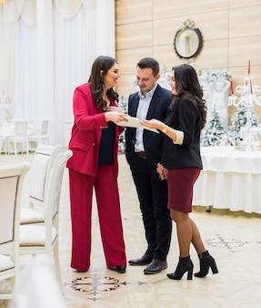 Giovani coppie e gestore di eventi che discutono programma