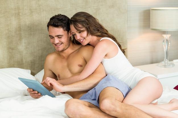 Giovani coppie facendo uso della compressa digitale e rilassandosi sul letto