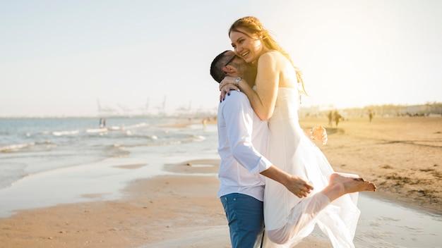 Giovani coppie felici amabili che abbracciano alla spiaggia