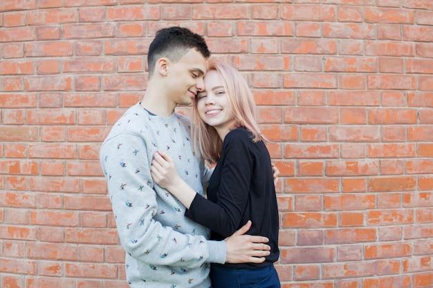Giovani coppie felici che abbracciano e che sorridono.