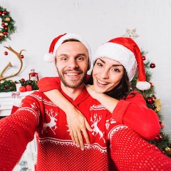 Giovani coppie felici che abbracciano in cappelli di natale