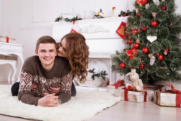 Giovani coppie felici che abbracciano vicino all'albero di natale che celebra insieme il nuovo anno che sorride