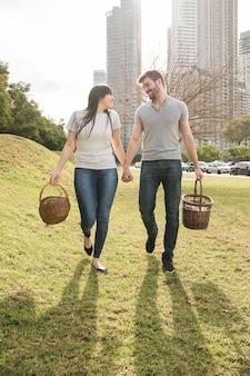 Giovani coppie felici che camminano con il cestino di vimini nel parco