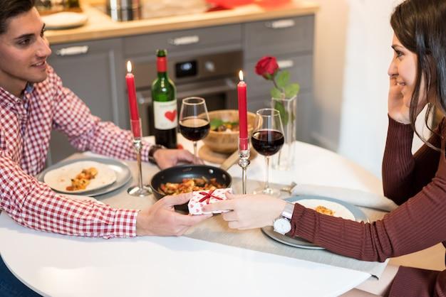 Giovani coppie felici che celebrano il san valentino con una cena a casa bevendo vino, evviva.