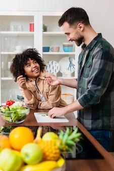 Giovani coppie felici che cucinano insieme