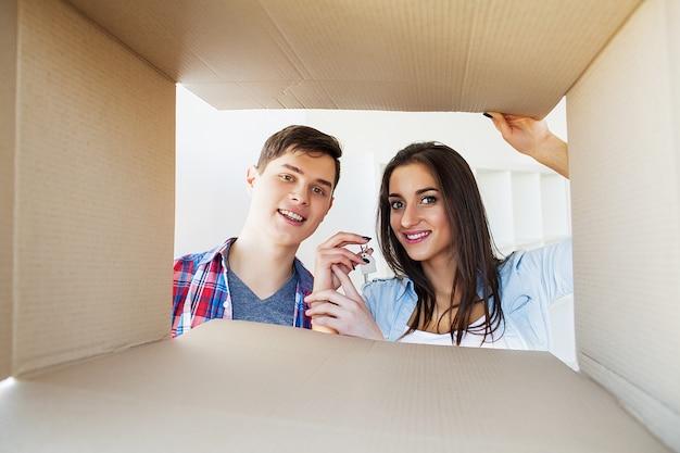 Giovani coppie felici che disimballano o che imballano le scatole e che entrano in una nuova casa
