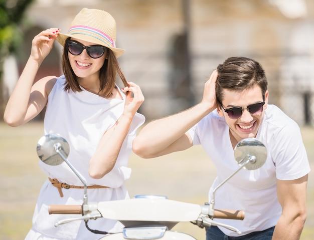 Giovani coppie felici che esaminano gli specchi di vista frontale del motorino.