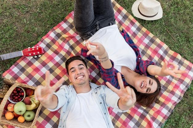 Giovani coppie felici che esaminano vista superiore della macchina fotografica