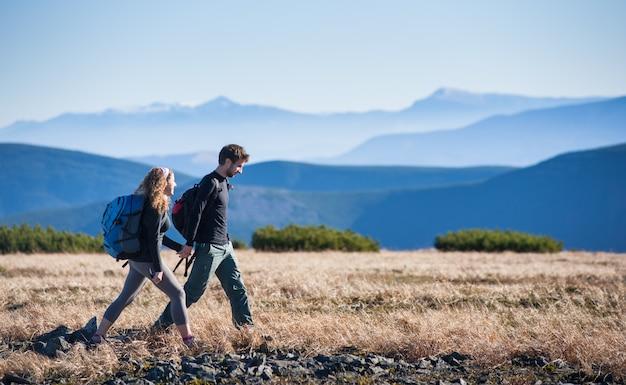 Giovani coppie felici che fanno un'escursione nelle belle montagne