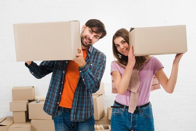 Giovani coppie felici che giudicano le scatole di cartone a disposizione